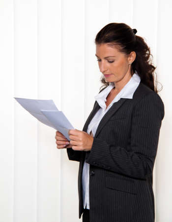 subpoena: Businesswoman reading a letter in the office. News of the lawyer or tax office.