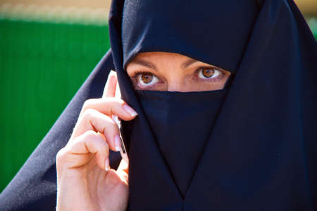 mobile telephones: Example picture Islam. Muslim burqa is with obscured. Stock Photo