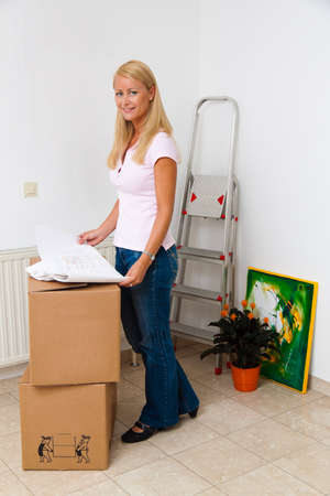 leases: Woman with cardboard boxes for moving into the new apartment.