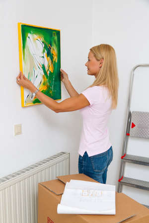 mietshaus: A young woman depends on screen when moving into new apartment. Stock Photo