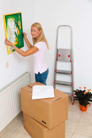 A young woman depends on screen when moving into new apartment. Stock Photo