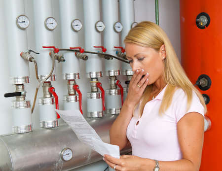energy supply: A young woman with a billing of heating costs for heating. In the boiler room.