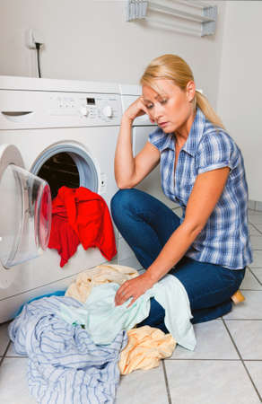 homemaker: A young housewife with washing machine and clothes. Washing day. Stock Photo