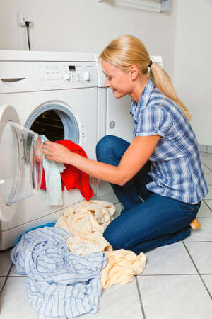 A young housewife with washing machine and clothes. Washing day. photo