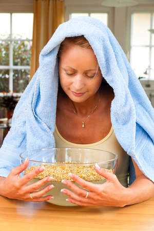 steam bath: A young woman with colds and flu. Inhalation of herbs.