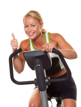 athletes: A young woman in training for endurance on exercise bike.