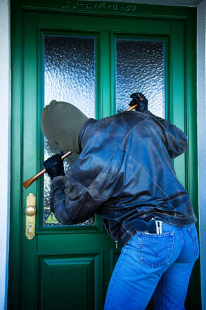 A burglar at the door of a house.