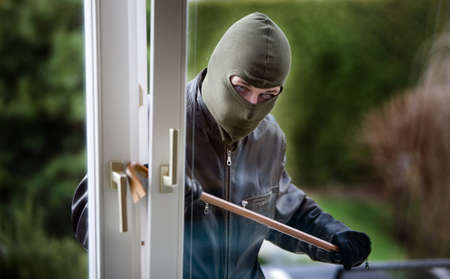 thieves: A burglar at a window of a house.
