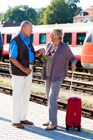 vital: Mature vital elderly couple at the train station. Traveling on vacation