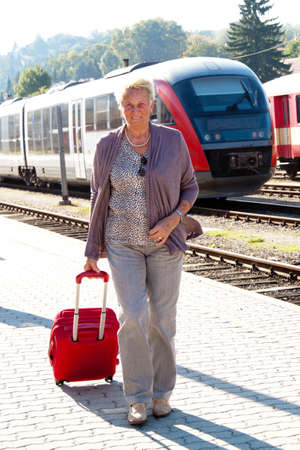 depart: Older vital senior woman at the station. Traveling on vacation