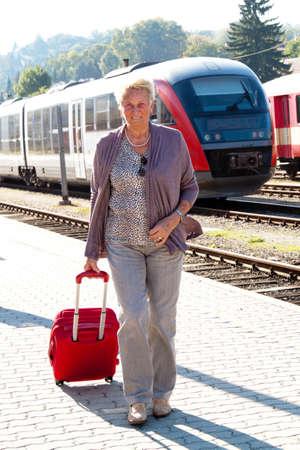 vital: Older vital senior woman at the station. Traveling on vacation
