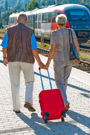 vigorously: Mature vital elderly couple at the train station. Traveling on vacation