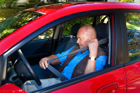strapping: Elderly man wearing a seatbelt when in a car.