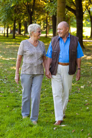 Mature couple in love seniors is walking in a park. photo