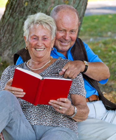 Mature couple in love senior citizens. Sitting in the park and read a book. Stock Photo - 7856864