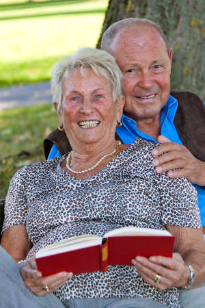 Mature couple in love senior citizens. Sitting in the park and read a book. Stock Photo - 7856882