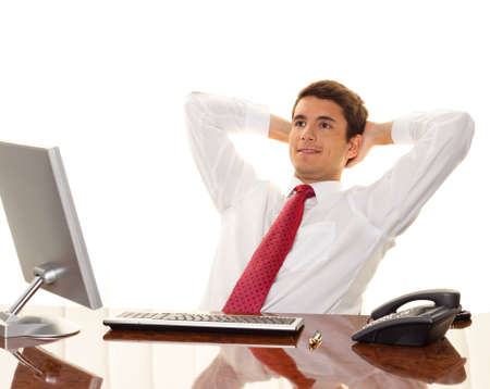 happy employee: A successful young manager sitting at a desk and smiles. Stock Photo