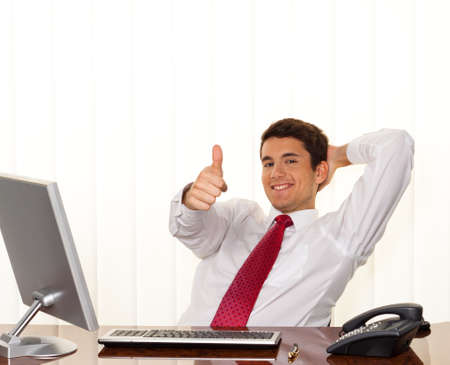 manager: A successful young manager sitting at a desk and smiles. Stock Photo
