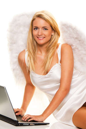 engel: Blonder Engel takes at Christmas wishes with a laptop. Stock Photo