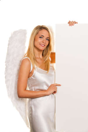 Blonde Angel for Christmas with an empty table for requests and offers. photo