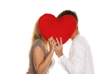 pareja besandose: Amantes de la pareja bes�ndose detr�s de un coraz�n. El amor es hermoso. Amor secreto