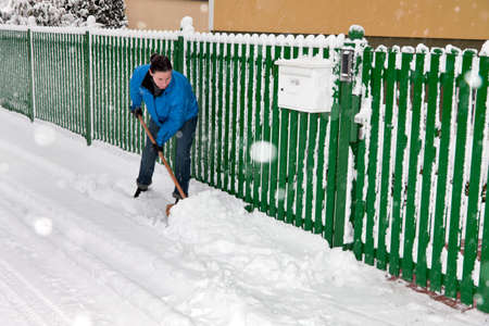 Woman is cleaning up snow. sweep with a broom snow. photo