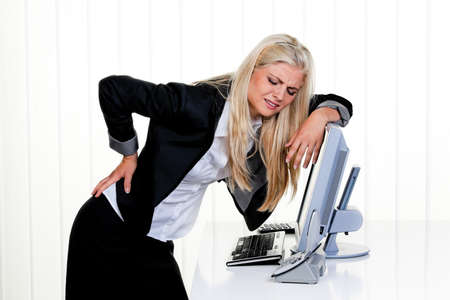 back ache: Young woman with pain in the back office. Stock Photo