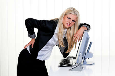 muscle tension tense: Young woman with pain in the back office. Stock Photo