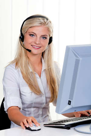 Young woman with headset at computer hotline. photo