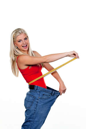 starvation: Young woman after a successful diet with great pants: Stock Photo