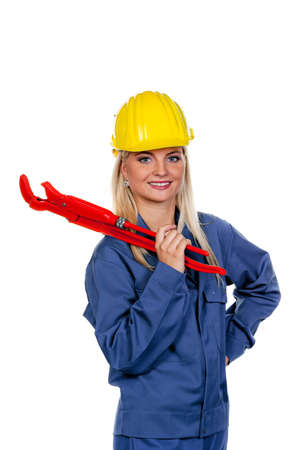 Young woman in blue work clothes with a pipe wrench. photo