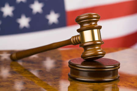 sentencing: A gavel in court. With an American flag in the background. Stock Photo