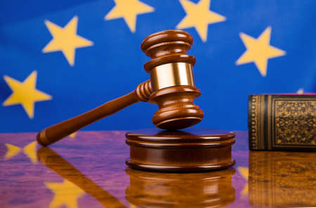 europeans: A gavel in court. With a European flag in the background.