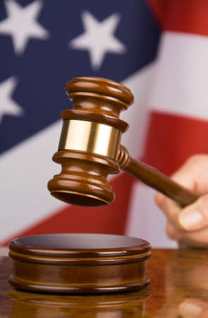 judging: A gavel in court. With an American flag in the background. Stock Photo