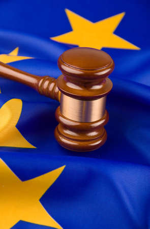 ruling: A gavel in court. With a European flag in the background.