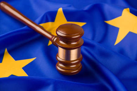 sentencing: A gavel in court. With a European flag in the background.