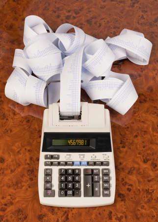 obligaciones: Calculadora de escritorio con franjas de equipo. S�mbolo de los costos, gastos, ingresos y beneficios.