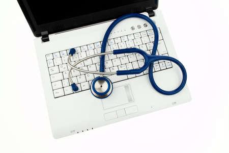 coordinacion: Un estetoscopio en un hospital se encuentra en el teclado del equipo.  Foto de archivo