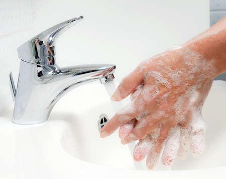 lavage mains: Femme lave les mains avec beaucoup d'eau et du savon. Protection contre l'infection de la grippe H1N1 nouvelle.