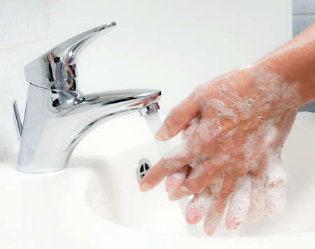 стирать: Woman washes with running water and soap hands. Protection from infection of the new flu H1N1.