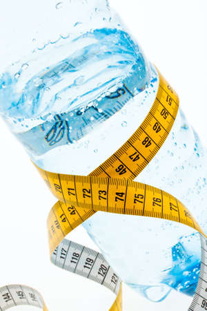 starvation: A plastic bottle of mineral water and measuring tape. Symbolic for diet.