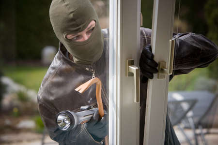 A burglar at a window of a house. photo