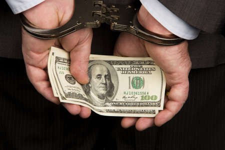 bribes: Handcuffs and dollar bills. Photo icon collar crime. Stock Photo