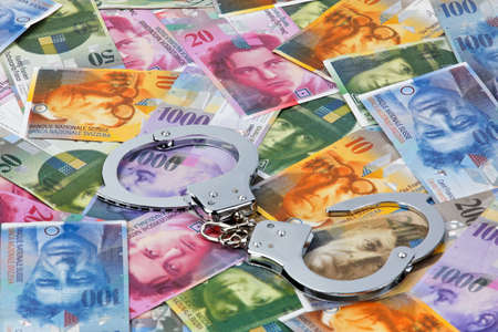 franc suisse: Swiss franc money and handcuffs. Crime in the economy Banque d'images