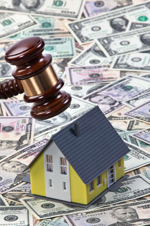 housing crisis: A house stands on many dollar bills. Real estate finance
