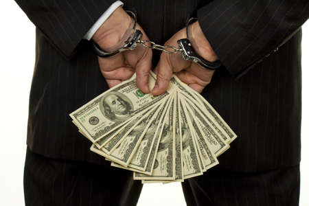 tax evasion: Handcuffs and dollar bills. Photo icon collar crime. Stock Photo
