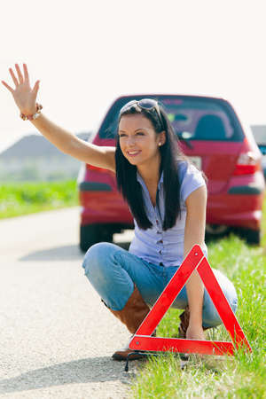 hedging: Young woman with a warning triangle in case of breakdown