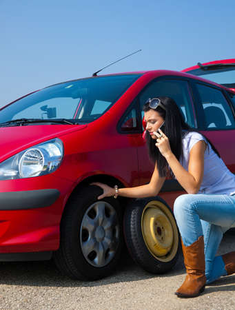 Young woman with a flat tire in car photo