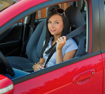 Young woman strapped to the seat belt in a car photo