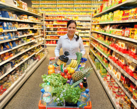 mercearia: Young woman with shopping cart in the supermarket when shopping.